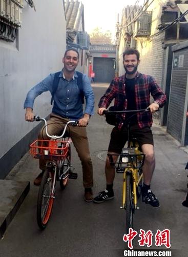 英国人Chris Georgiou(左)和朋友在北京骑共享单车逛胡同。受访者供图